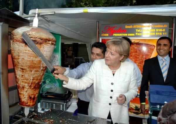 Меркель интересуется приготовлением шаурмы.